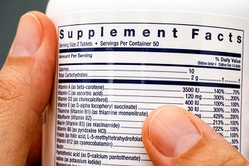 Person reads supplement label