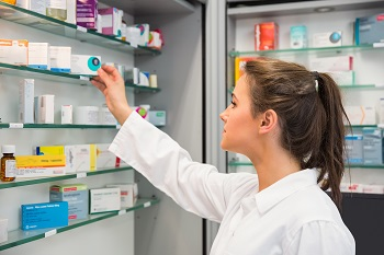 Pharmacist takes medicine from a shelf